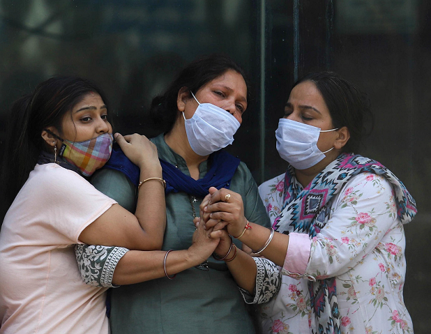 At a crematorium in New Delhi, India, women mourn a person who died of COVID‑19. Photo by Vijay Pandey/ZUMA Wire/Alamy